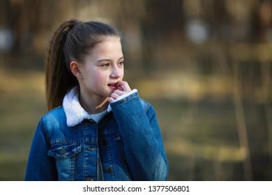 Twelve-year-old girl in a denim jacket posing in a summer pine Park.