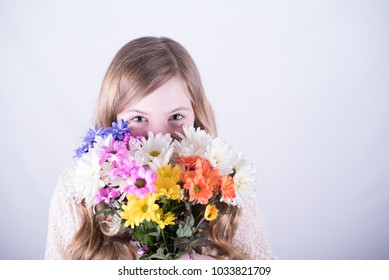 Twelve-year-old girl with long, dirty blonde hair holding colorful bouquet of daisies over lower face with smiling eyes open against white background