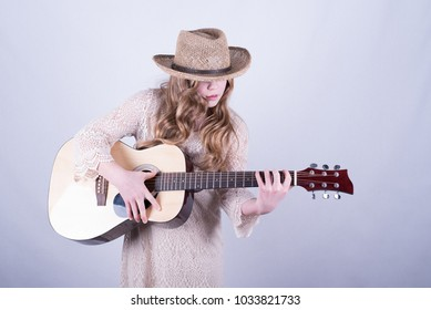Twelve-year-old girl with long, dirty blonde hair and wearing straw hat covering eyes playing acoustic six-string guitar against white background