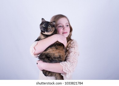 Twelve-year-old girl with long, dirty blonde hair holding a tortoiseshell cat while looking to the side against white background