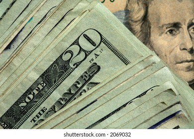 Twenty dollar bills stacked in diagonal array showing Jackson's face in the background.