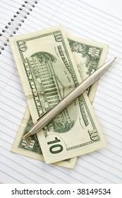 Twenty dollars, pen on background with paper