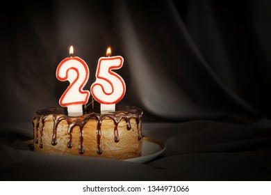 Twenty five years anniversary. Birthday chocolate cake with white burning candles in the form of number Twenty five. Dark background with black cloth