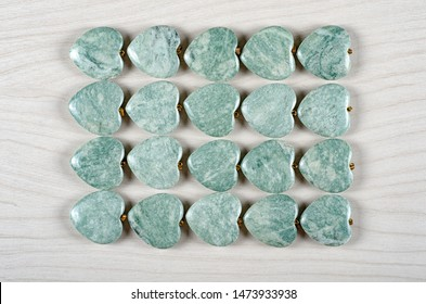Twenty green amazonite heart-shaped stones are stowed four rows. Five pieces in each one. Top view.