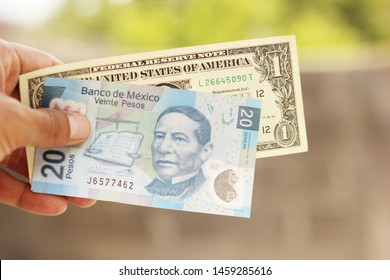 Twenty Mexican pesos bill with an American dollar.