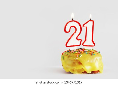 Twenty one years anniversary. Birthday cupcake with white burning candles with red border in the form of number Twenty one. Light gray background with copy space