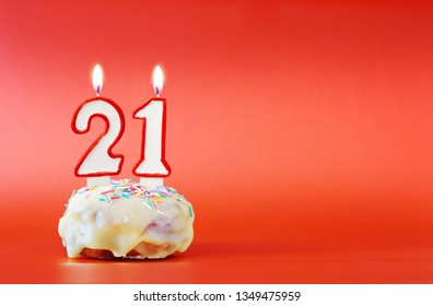 Twenty One Years Birthday Cupcake With White Burning Candle In The Form Of Number 21