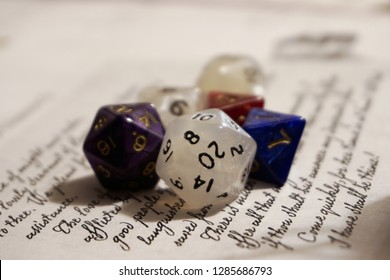 Twenty sided and other polyhedron dice for role playing games on a letter background