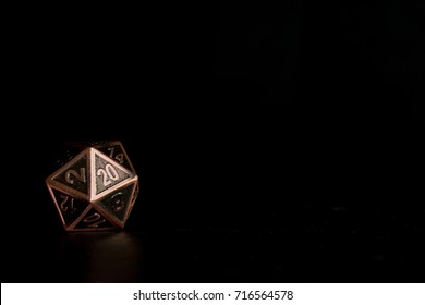 A twenty sided  polyhedral die on a slate surface. These type of dice are used for role playing games.
