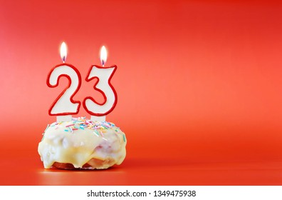 Twenty three years birthday. Cupcake with white burning candle in the form of number 23. Vivid red background with copy space