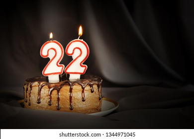 Twenty two years anniversary. Birthday chocolate cake with white burning candles in the form of number Twenty two. Dark background with black cloth