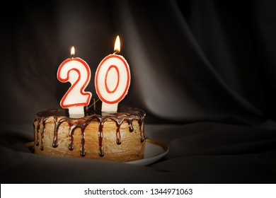 Twenty years anniversary. Birthday chocolate cake with white burning candles in the form of number Twenty. Dark background with black cloth