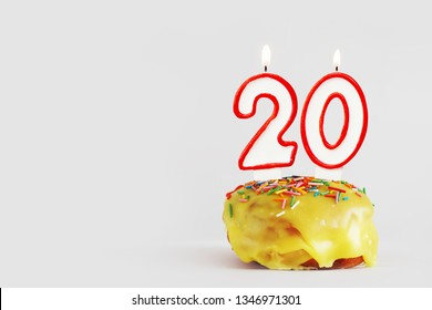 Twenty years anniversary. Birthday cupcake with white burning candles with red border in the form of number Twenty. Light gray background with copy space