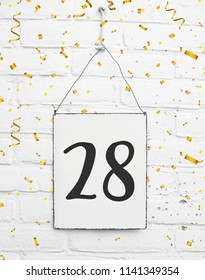 Twenty-eight years old birthday congratulations text with golden confetti sign white brick background number 28
