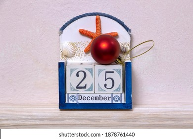 Twenty-fifth of December, December 25th, closeup view of wooden  blocks color calendar on a marine theme with red Christmas tree decoration. Christmas and New Year theme, neutral beige background.