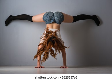 twerk redhead woman in jeans shorts on blue background