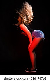 Twerking young woman over black background