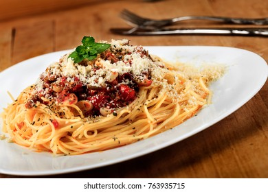 Twig of fresh lemon basil on Spaghetti. Pasta with cherry tomatoes sausage