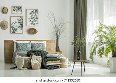 Twigs with leaves placed in a bottle shaped vase standing on a small table in white bedroom with paintings