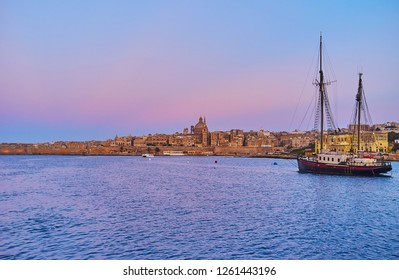 The twilight above the medieval city of Valletta with a view on its architecture, Northern Harbour and vintage sailing ship on the foreground, Malta.