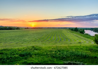 Twilight at cultivated land in the countryside on a summer evening with cloudy sky background and river. Procurement of food for animals. Combined field. Landscape.