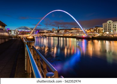 Twilight at Gateshead Millennium Bridge / The Quayside at Newcastle on the banks of the River Tyne, with its famous bridges and Newcastle upon Tyne skyline beyond, seen here at night