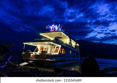 Twilight houseboat dance party featuring a  night sunset sky, lake, beach and boat. This horizontal, long exposure shot was taken with a low angle view looking up on Shuswap Lake in British Columbia.