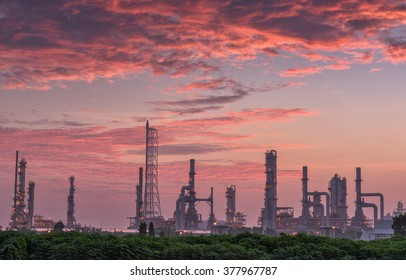 Twilight of oil refinery plant on red cloudy background.