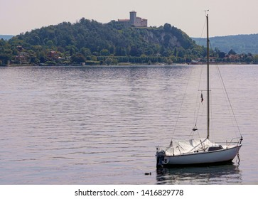 twilight on Lake Maggiore, sailing boat moored with Angera castle in the background. Italy