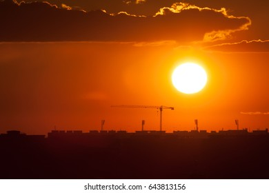 Twilight over the city of Bucharest. Construction crane, building silhouettes and sun circle in the background.