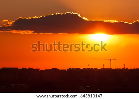 Twilight over the city of Bucharest. Construction crane and building silhouettes in the background.
