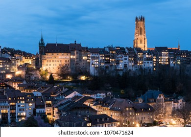Twilight over the Fribourg old town and the illuminated Cathedral Saint Nicolas in Switzerland. Fribourg is one of the best preserved medieval old town in the country.