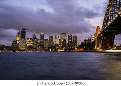 Twilight over the Sydney downtown district skyline by the Sydney harbor, and the famous bridge, in Australia largest city.