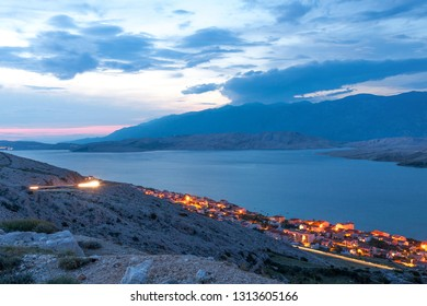 Twilight panorama of Pag town on Pag island with Velebit mountains on background, Kvarner, Croatia