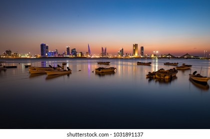 Twilight rises over the Manama skyline with small fishing boats in the foreground.