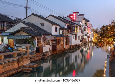 Twilight scene in Suzhou, China with historical houses along the Pingjiang Lu canal