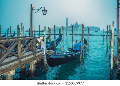 twilight scenery with gondola near pier from Venice, Italy