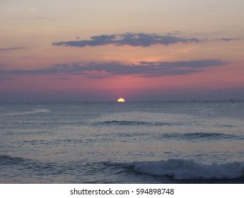 Twilight seascape at sunrise on the beach with half of yellow, golden sun is below the horizon with orange, pink sky, red sky and dark clouds and waves at the sea