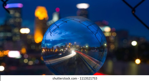 Twilight shot through glass ball of 24th Street pedestrian bridge, through the fencing over 35W highway Minneapolis Minnesota USA