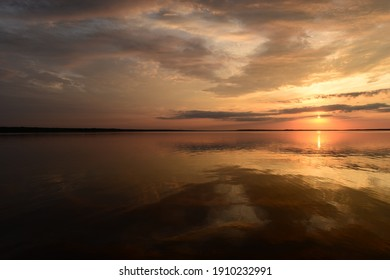 Twilight sky in colorful bright sunlight reflects off on the water surface