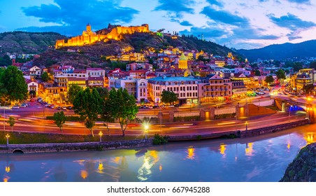 The twilight sky over the old Tbilisi, the bright lights of Narikala fortress and Old Town neighborhood are reflected in muddy waters of Kura river, Tbilisi, Georgia.