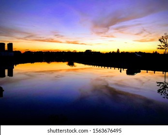 Twilight sky with purple, orange and gold shades. With a reflection of sky on water. On a still river or waterbed.