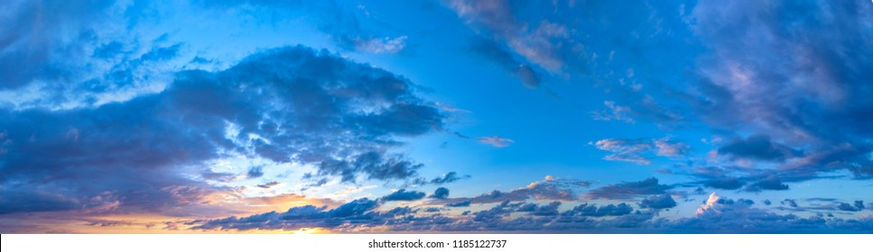 Twilight sunset with colorful clouds. Dramatic atmosphere created by the sunlight. Colorful gradient from blue to orange. Blue sky and clouds. High resolution panoramic sky.