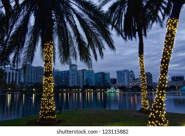 Twilight view of Orlando skyline during the Christmas holidays. Lake Eola and decorated palm trees in foreground.
