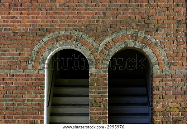 Twin arched doorways with steps leading up from the street in an old red brick European building