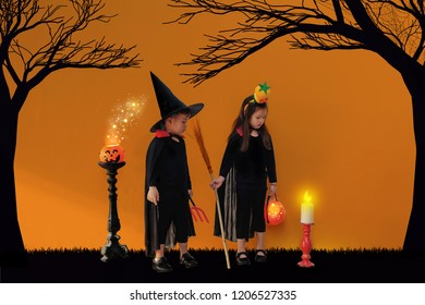 Twin Asian little boy and girl in Haloween costume with pumpkin on Haloween decor background. Halloween, carnival, childhood, fairytale theme.