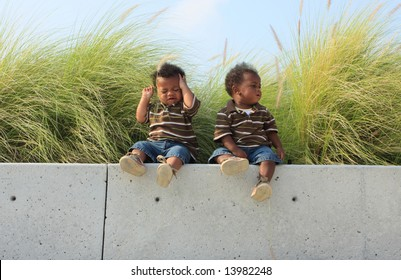 Twin Babies Sitting on a Ledge.