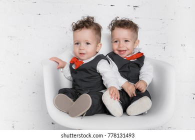 Twin baby boys are sitting in the studio