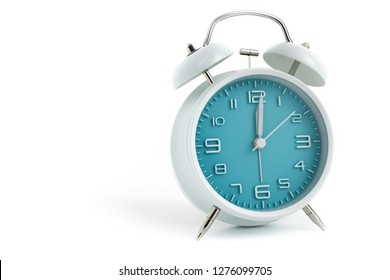 Twin bells analogue alarm clock with turquoise clock face shows 1 past 12, 12.01 AM PM; concept on white background