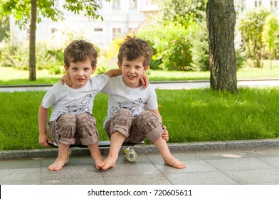twin boys embraced sitting on skateboard outdoors in park